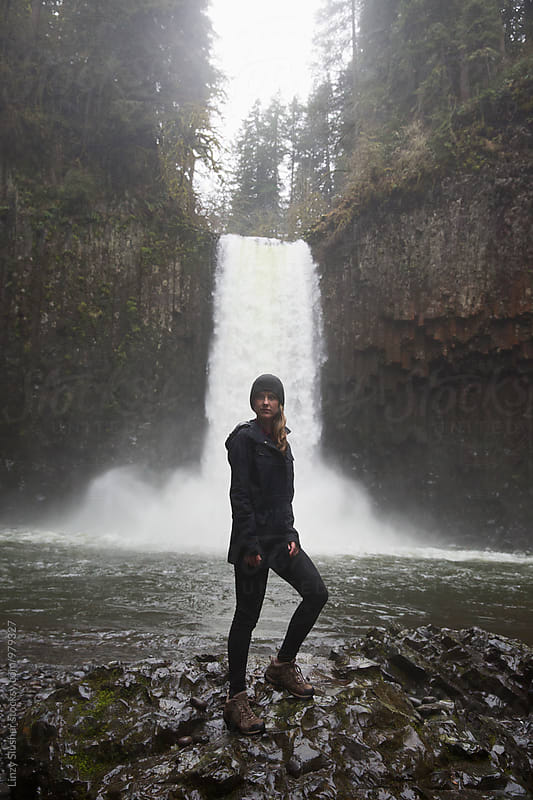 Gloomy female hiker standing near waterfall by Linzy Slusher for Stocksy United