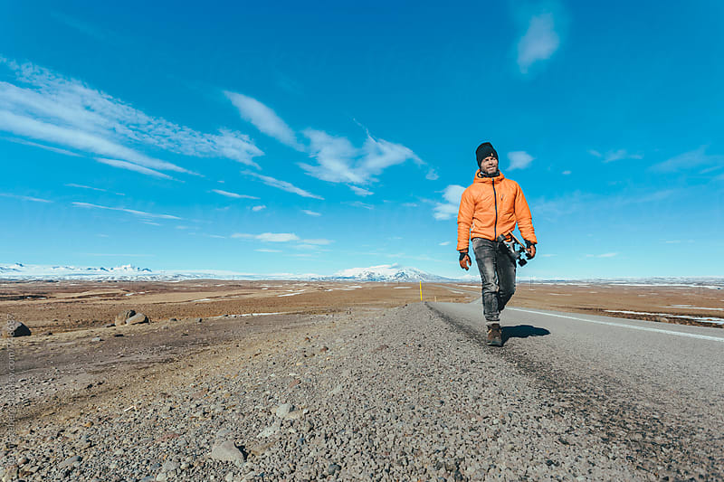 Mand walking with skateboard on mountain road by Søren Egeberg Photography for Stocksy United