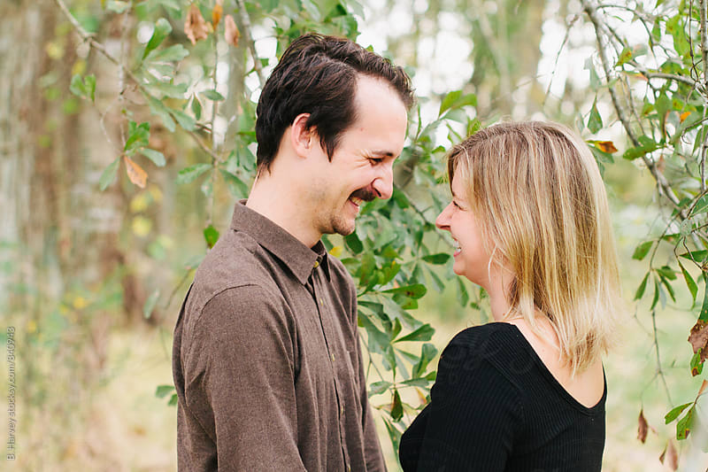 Cute Couple Laughing and Smiling Surrounded by Tree Branches by B. Harvey for Stocksy United