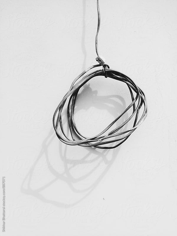 An old wire hanging against a white background. by Shikhar Bhattarai for Stocksy United