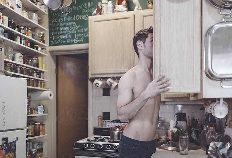 Shirtless Man Reaching for something from Cabinet of Small Kitchen in Urban Apartment by Joselito Briones for Stocksy United