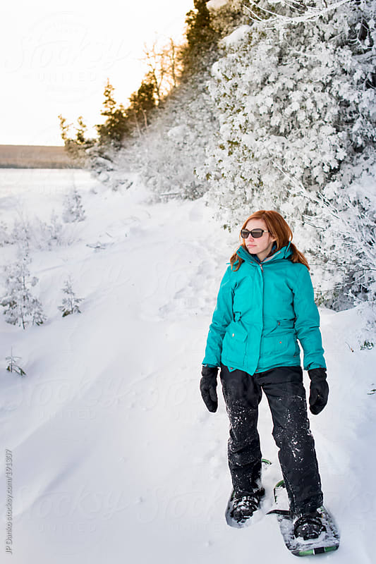Woman With Snowshoes In Snow On Northern Lake by JP Danko for Stocksy United