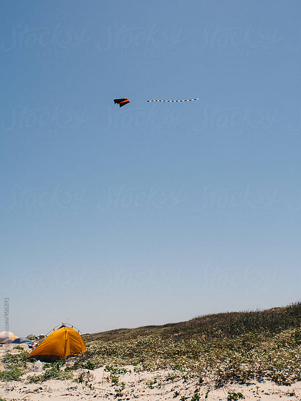 Kite flying above tent at the ocean by Jeremy Pawlowski for Stocksy United