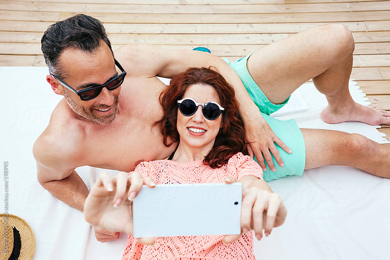Beautiful couple taking photos of himself with smart phone camera. Summer time. by BONNINSTUDIO for Stocksy United