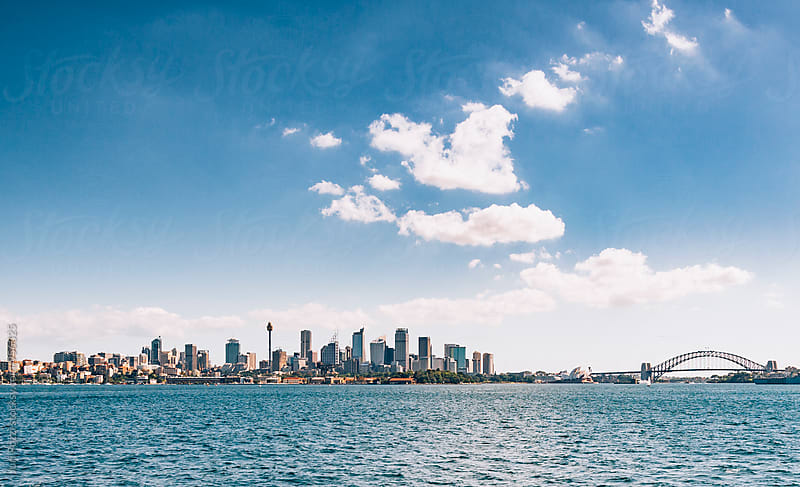 Sydney skyline seen from the bay by Juri Pozzi for Stocksy United
