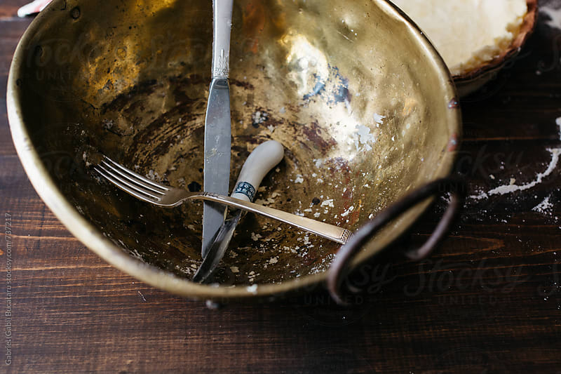 Old brass mixing bowl with fork and knives by Gabriel (Gabi) Bucataru for Stocksy United