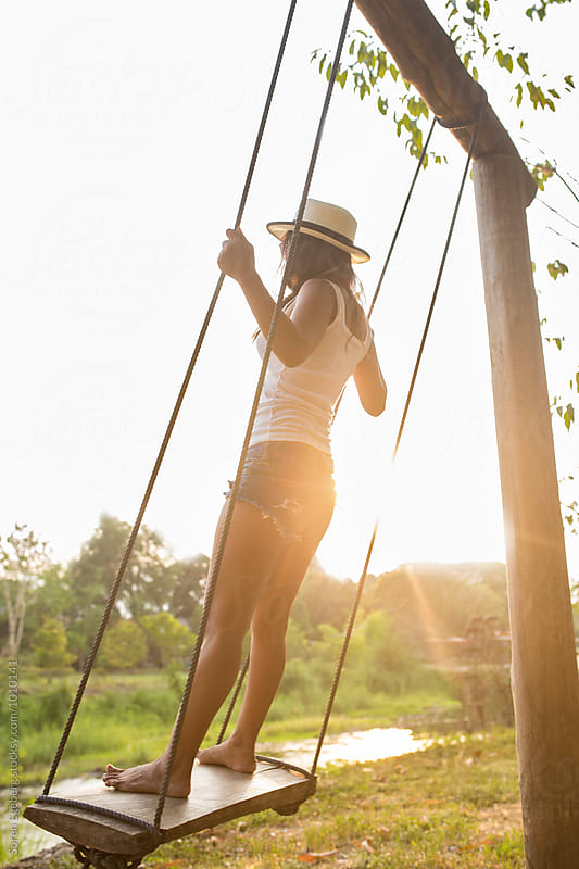 Summer girl on a swing at sunset by Soren Egeberg for Stocksy United