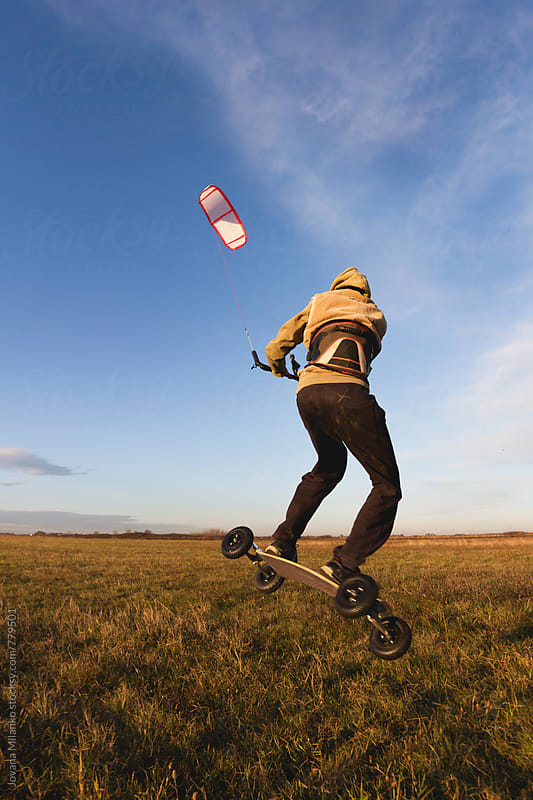 Young man jumping with his ATB and kite in the field at sunset by Jovana Milanko for Stocksy United