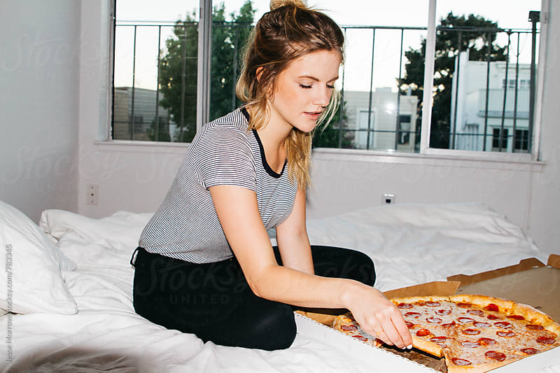 young female grabs slice of full pepperoni pizza by Jesse Morrow for Stocksy United
