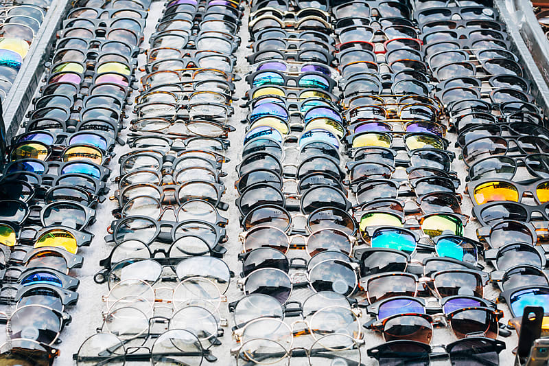 Street vendors table filled with sunglasses. New York City. by Kristin Duvall for Stocksy United