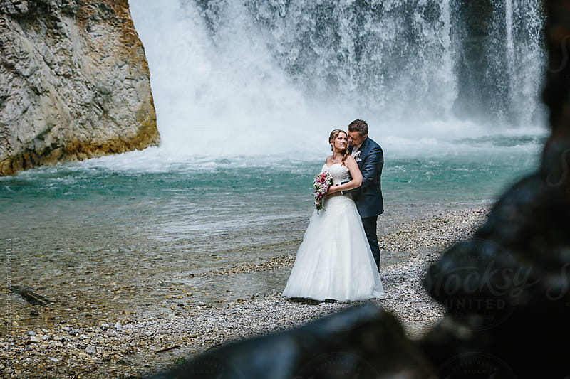 loving bride and groom standing  in front of a big waterfall on a rocky beach by Leander Nardin for Stocksy United