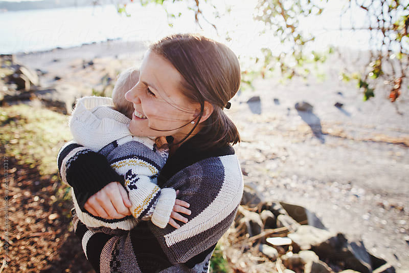 Young mom enjoying hugging with son outside at the beach by Rob and Julia Campbell for Stocksy United