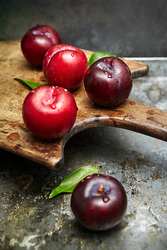 Five plums on a wooden chopping board by James Ross for Stocksy United