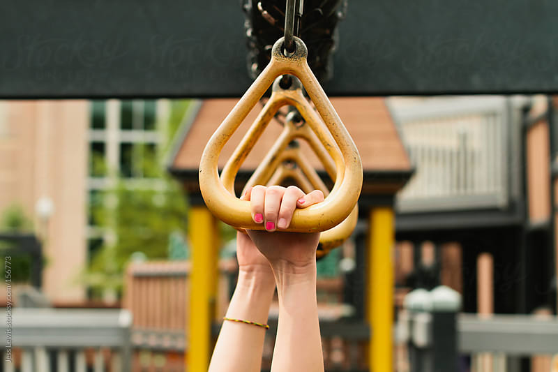 girl's hands holding playground equipment by Jess Lewis for Stocksy United