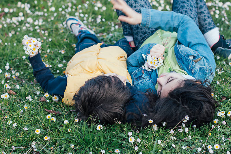 Siblings having fun lying on the grass in a park by Beatrix Boros for Stocksy United
