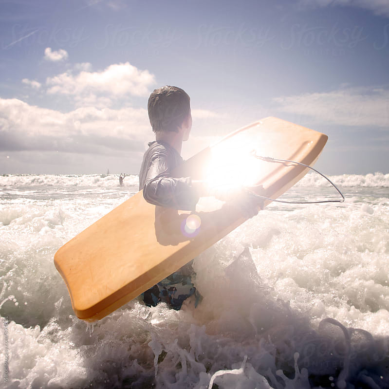 Boy with his bodyboard walking into the ocean by Marcel for Stocksy United
