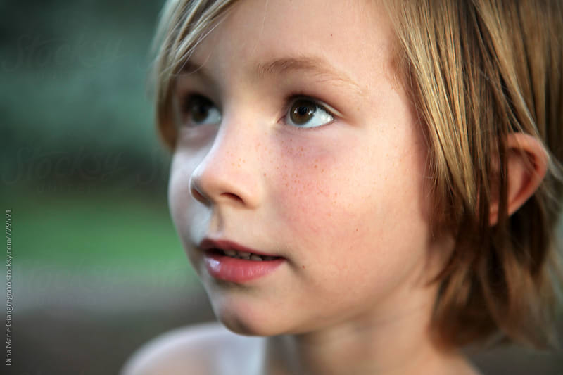 Little boy with Long Hair and Freckles by Dina Giangregorio for Stocksy United
