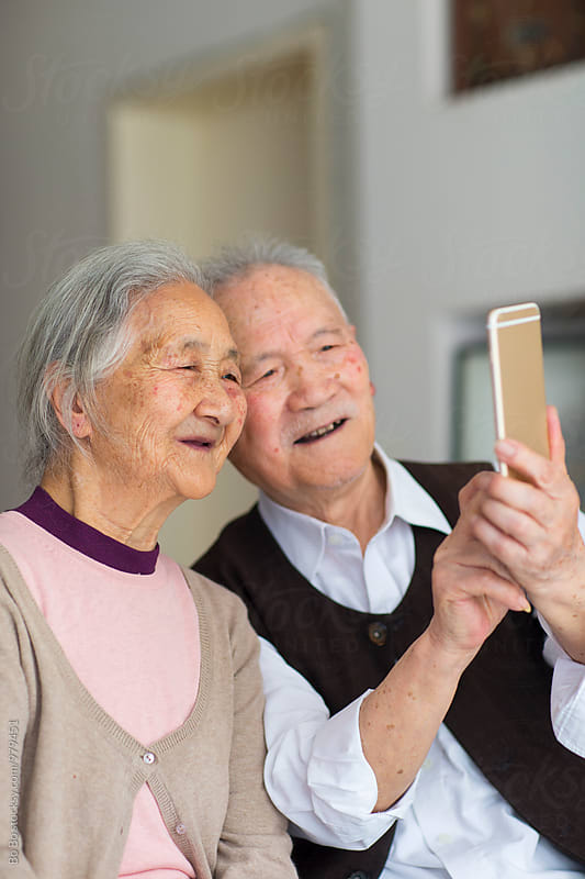 senior asian couple using smart phone indoor by cuiyan Liu for Stocksy United