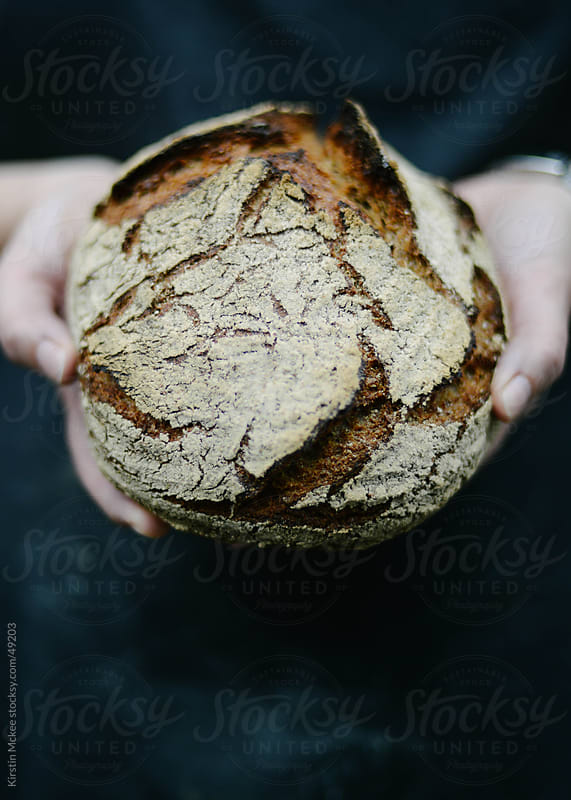 Holding a loaf of freshly baked rye bread.  by Kirstin Mckee for Stocksy United