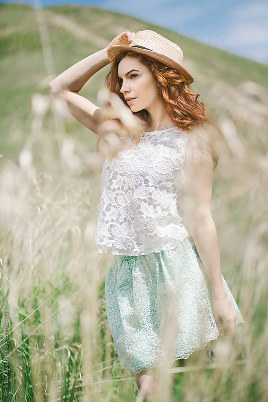 Redhead girl standing in a field in the summer by Ania Boniecka for Stocksy United