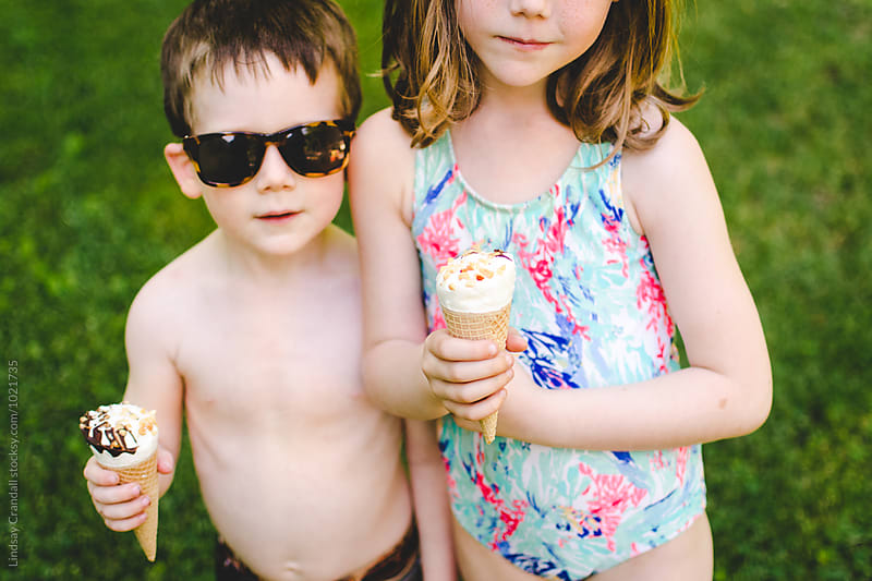 Brother and sister standing together while holding ice cream cones by Lindsay Crandall for Stocksy United