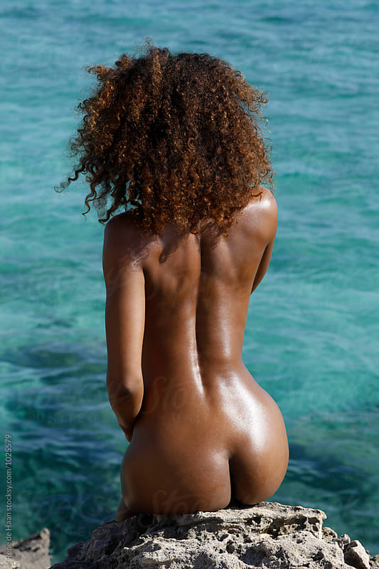 behind of young black woman at sea by Rene de Haan for Stocksy United