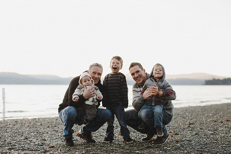Multigenerational family at beach having fun together posing for picture by Rob and Julia Campbell for Stocksy United