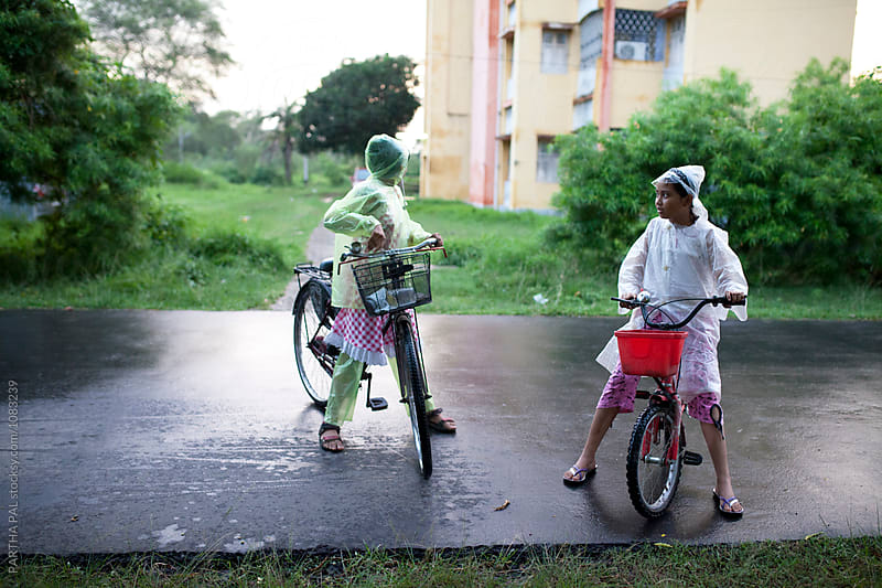 Teenagers wearing rain proof and gossiping on road by PARTHA PAL for Stocksy United