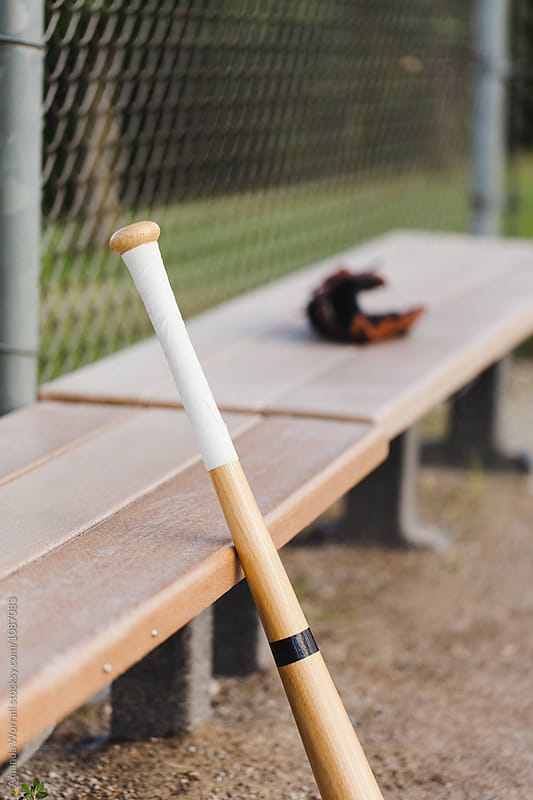 Baseball bat leaning against the dugout bench by Amanda Worrall for Stocksy United