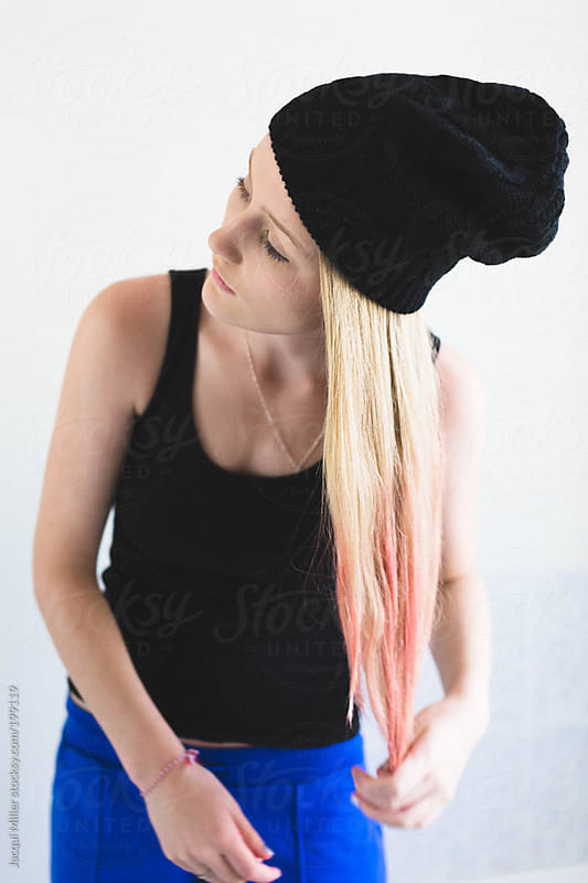 Teenage girl putting pink hair day on the tips of her long blonde hair by Jacqui Miller for Stocksy United