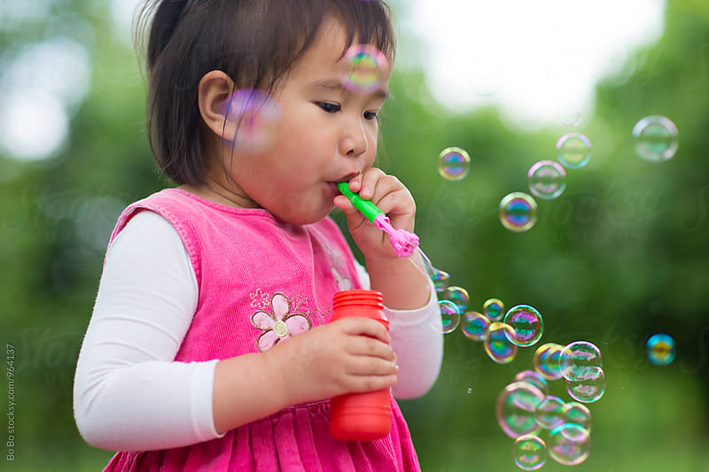 little asian girl blowing soap bubble outdoor by Bo Bo for Stocksy United