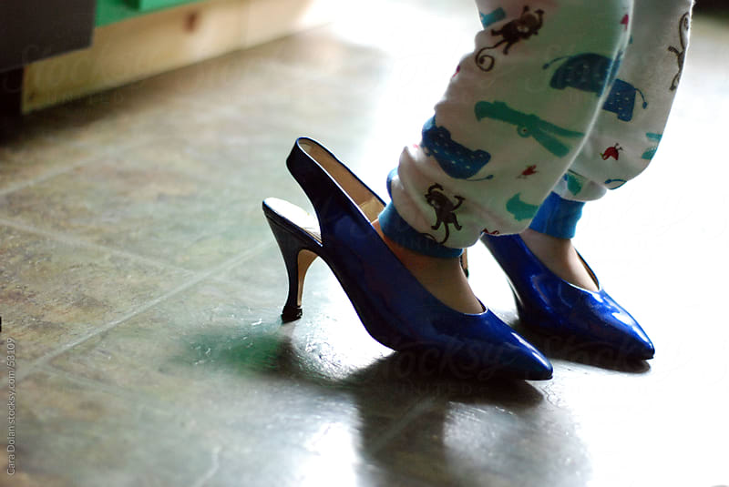 Child wearing his mother's blue high heeled shoes by Cara Dolan for Stocksy United