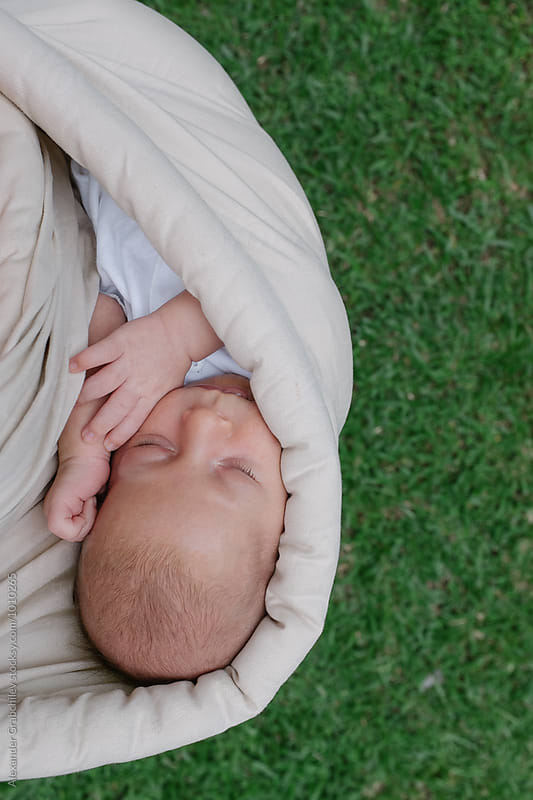 Baby boy in a sling  by Alexander Grabchilev for Stocksy United