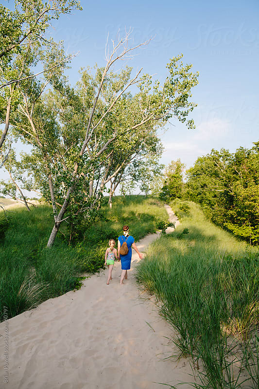 mom and daughter walk at Warren Dunes State Park by Brian Powell for Stocksy United