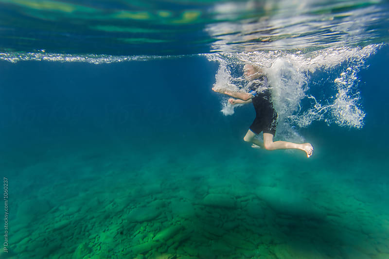 Underwater Boy Jumping Into Summer Lake From Water Trampoline At Cottage by JP Danko for Stocksy United