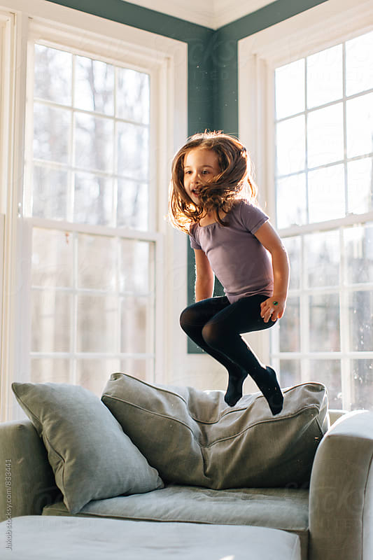 Young girl in a dance outfit jumping on an oversized chair by Jakob for Stocksy United