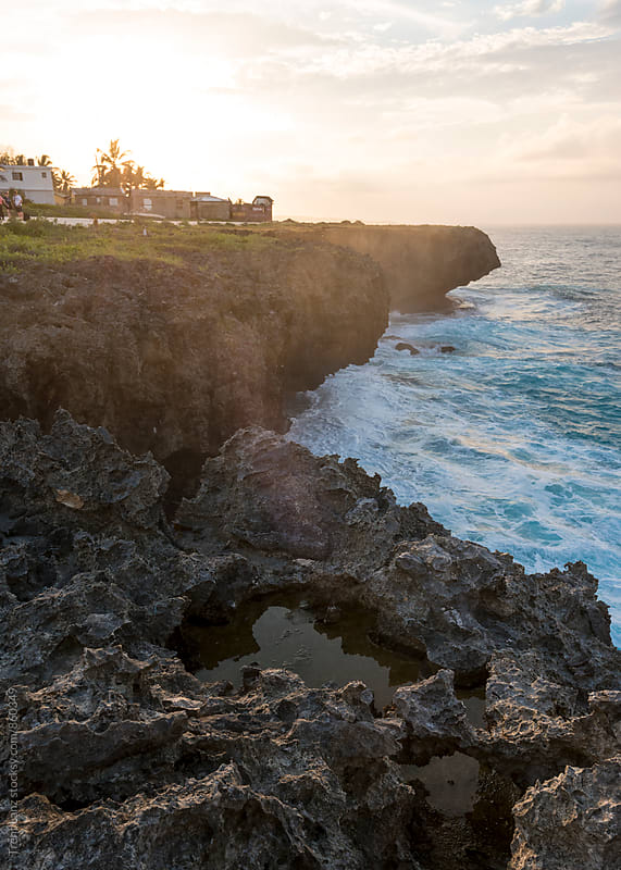 Rocky ocean coastline in sunlight during sunset by Trent Lanz for Stocksy United