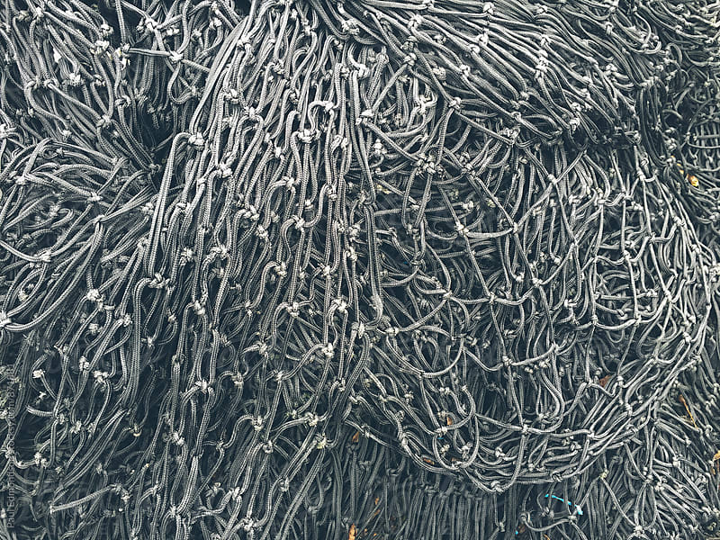 Close up of piles of commercial fishing nets  by Paul Edmondson for Stocksy United