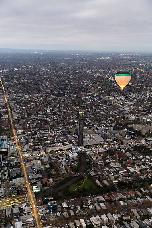 Black green and white hot air balloon hovering above urban scene and streets by Ben Ryan for Stocksy United
