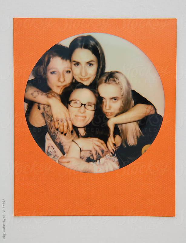 Polaroid photo of four friends looking at the camera  by kkgas for Stocksy United