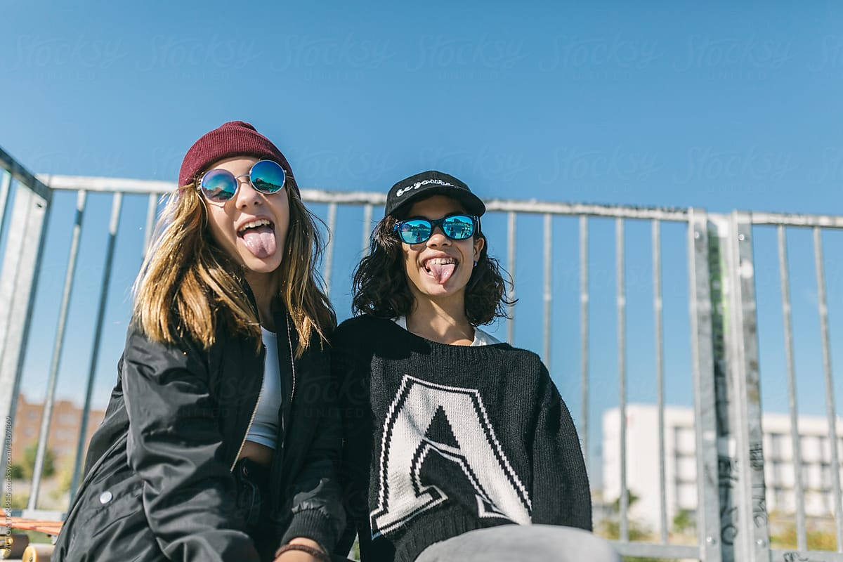 Stock Photo - Two Teen-Age Hipster Girls Put Out Their Tongue