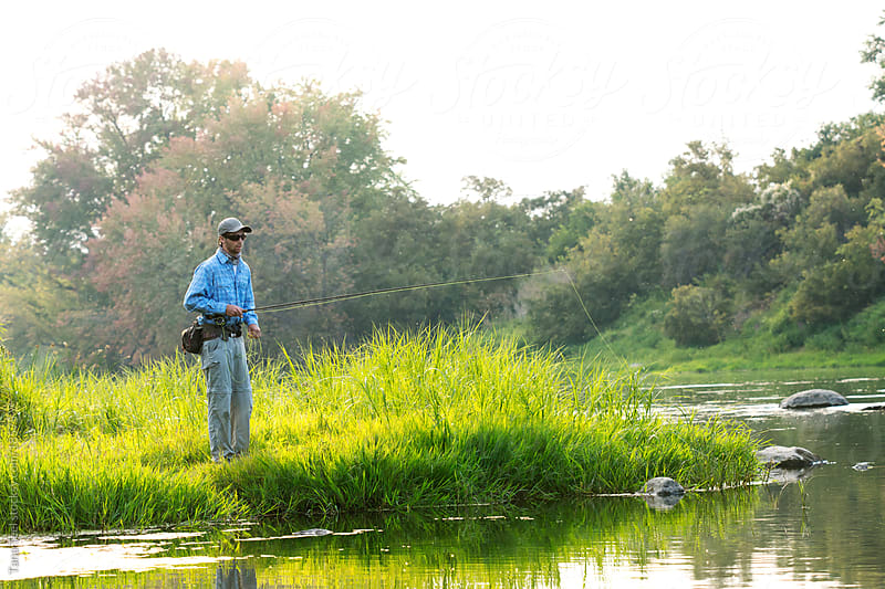 A young man fishing along bank of river.  by Tana Teel for Stocksy United