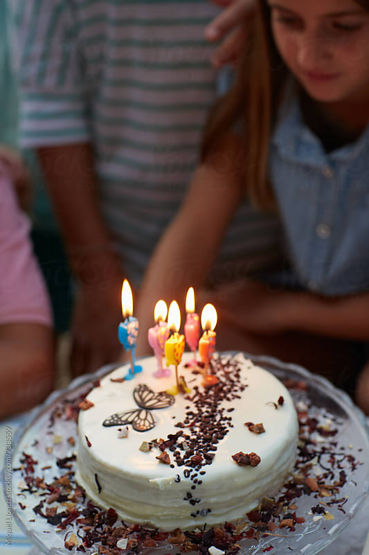 Close up of a birthday cake with candles and children by Miquel Llonch for Stocksy United