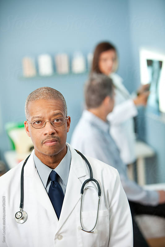 Exam Room: Serious African American Doctor in Office by Sean Locke for Stocksy United