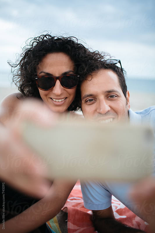 Happy couple taking selfie photo on the beach by Davide Illini for Stocksy United