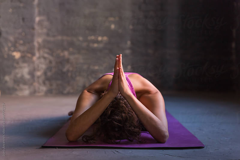 Woman practicing yoga in a studio by Jovo Jovanovic for Stocksy United