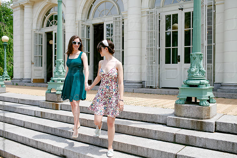 two women on stairs in front of public park building  by Jennifer Brister for Stocksy United