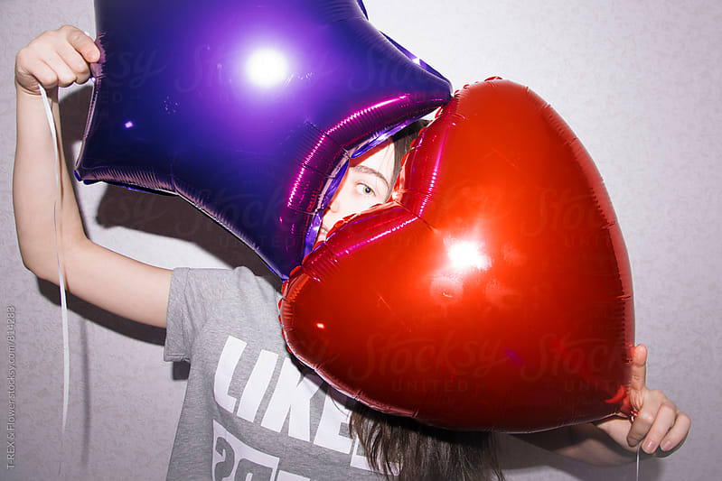 Young woman looking out of two balloons by Danil Nevsky for Stocksy United