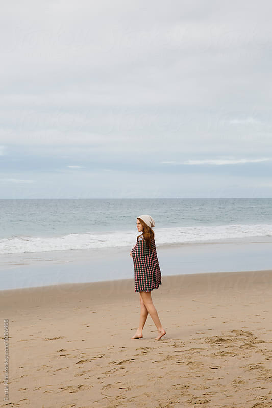 Woman walking on the beach with blanket over her by Curtis Kim for Stocksy United