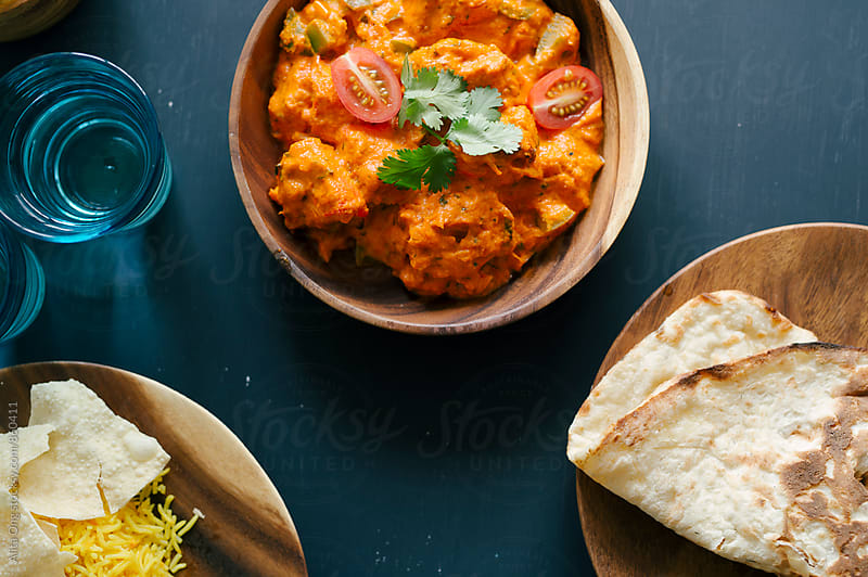 Chicken tikka masala served with naan by Alita Ong for Stocksy United